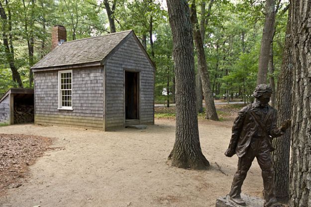 Replica of Thoreau's cabin, and his statue, near Walden Pond. Wikimedia Commons